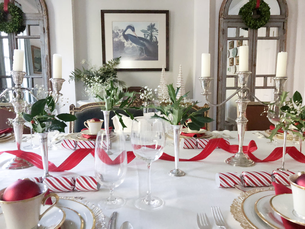 Finally, red linen napkins and a red ribbon tie the colors of the table together while giving a nod to our traditional southern style. The eye-catching shine of silver and gold, the pops of vivid red and green, and the combination of elements and accents both cherished and new: our table honors the past, celebrates the present, and heralds a bright new year.