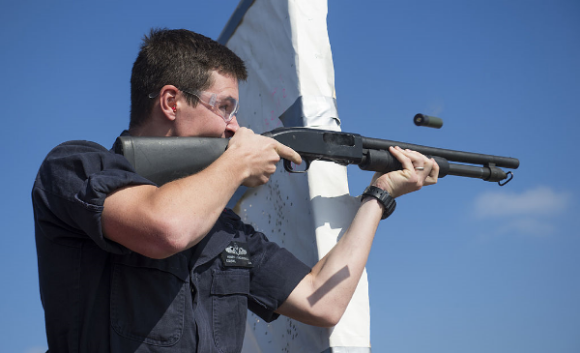 Firing a Mossberg 500 12-gauge shotgun on the flight deck of dock landing ship USS Comstock.