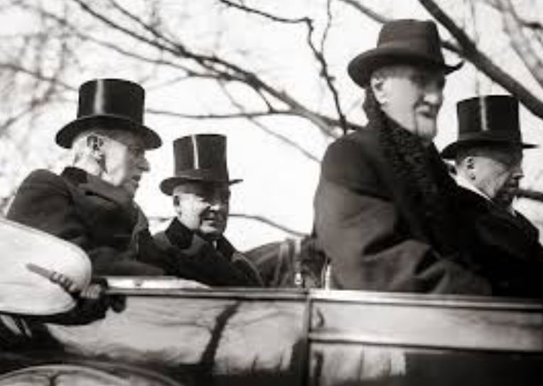 Warren G. Harding wearing a top hat, traveling to his inauguration.