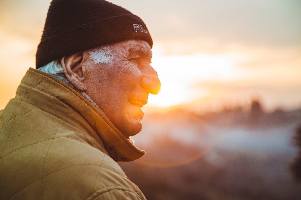 Elderly man outside, older man listening