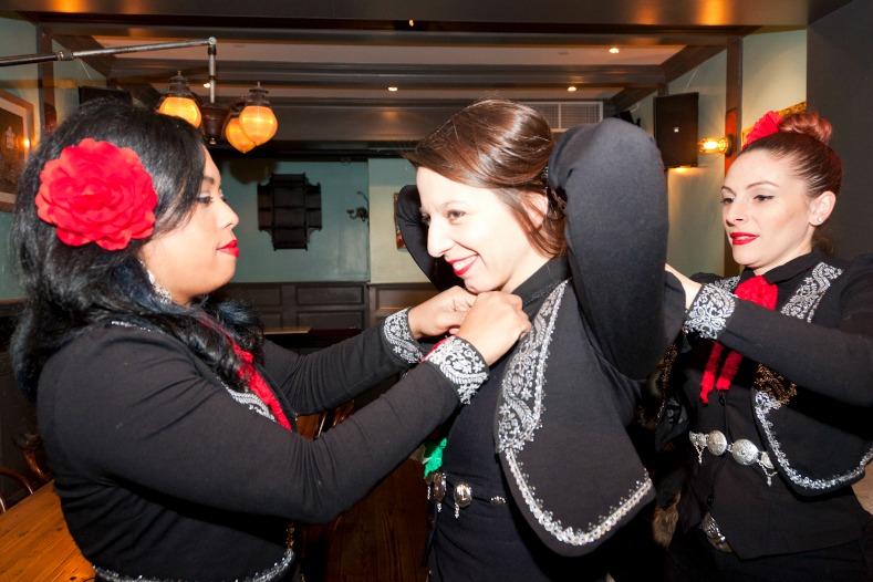 Members of Mariachi Flor De Toloache help Mallozzi adjust her costume.