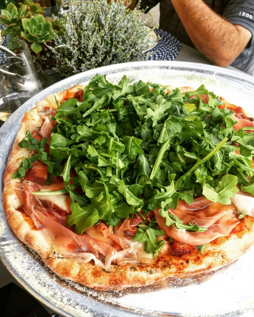 Pizza with tomato sauce, prosciutto and arugula