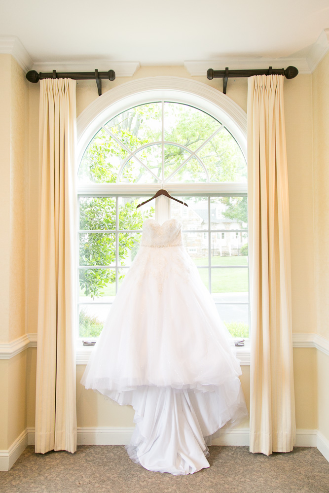 Wedding dress hanging in the window of Evergreen Country Club | Northern Virginia Wedding Photography