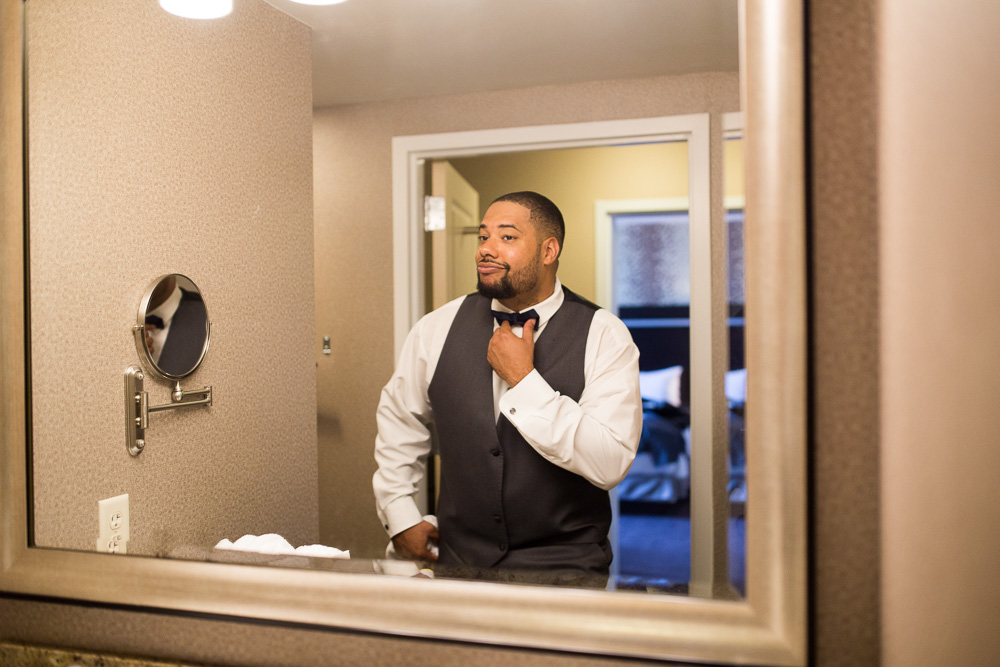 Groom looking in the mirror | Rochester Wedding Photography