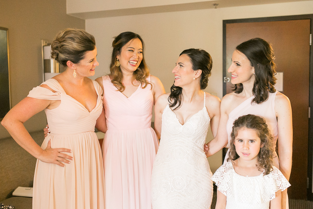 Bride laughing with her bridesmaids while getting ready at Hyatt Place | DC Wedding Photographer