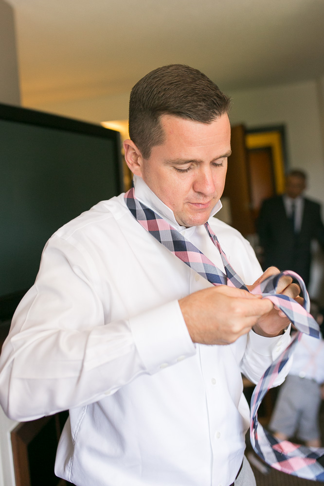 Groom tying his tie | Getting ready photos at Hyatt Place Chantilly/Dulles