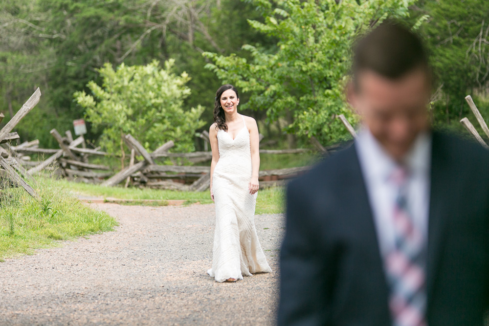 Smiling bride approaching the groom for the First Look photos | Stone Bridge at Manassas National Battlefield Park