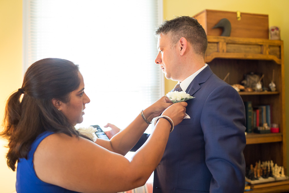 Groom putting on his boutonniere | Candid wedding photography