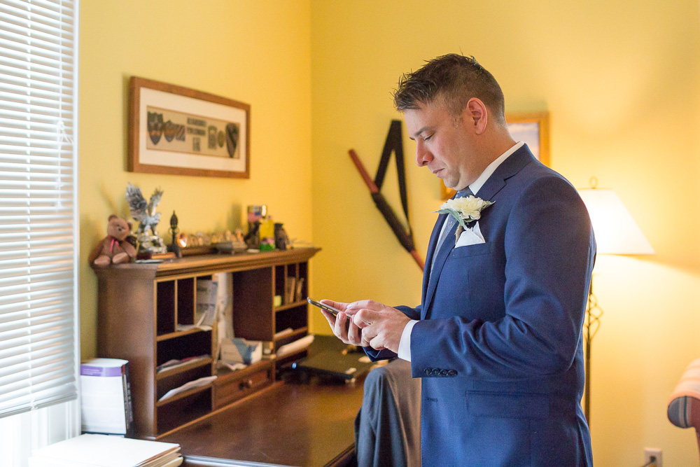 Groom getting ready and checking the forecast on his phone | Rainy day wedding