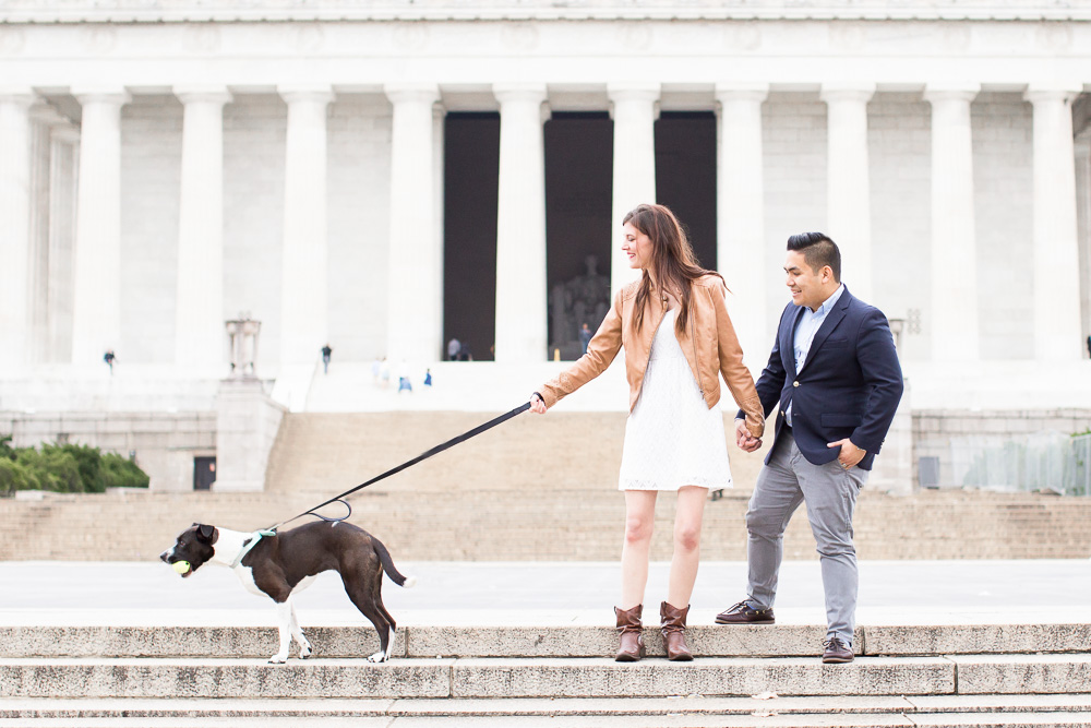 Fun photo of engaged couple with their dog in front of the Lincoln Memorial | Candid Washington DC Engagement Photographer | Megan Rei Photography