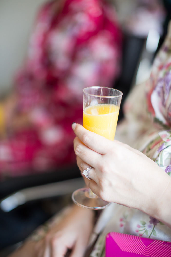 Bride holding her mimosa while getting ready for the wedding day | Getting ready photos at the Westin Washington Dulles