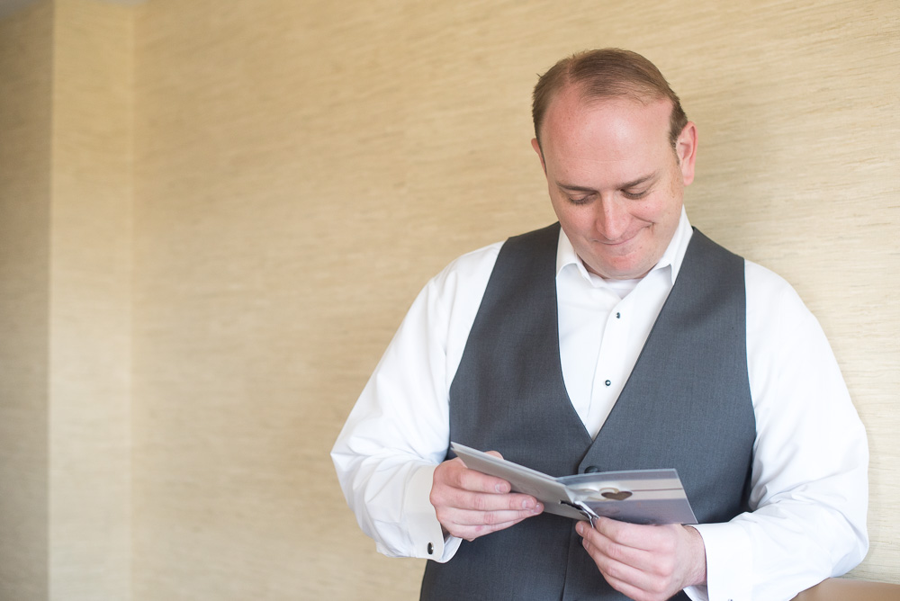Groom reading a sweet letter from the bride before the wedding ceremony | Westin Washington Dulles Airport Wedding | Candid Wedding Photographer in Herndon, VA