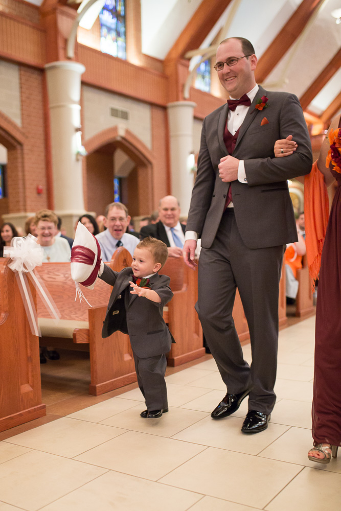 Ring bearer running down the aisle at St. Theresa Parish in Herndon, VA | St. Theresa Wedding Ceremony