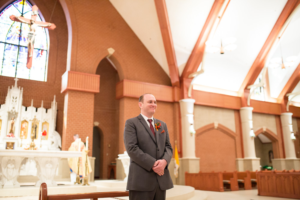 Groom watching the bride walk down the aisle at Saint Theresa's in Ashburn | Northern Virginia Candid Wedding Photographer