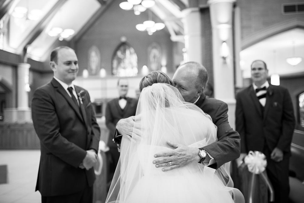 Father of the bride giving her a hug at the altar of St. Theresa Church | Ashburn Virginia Wedding Photographer