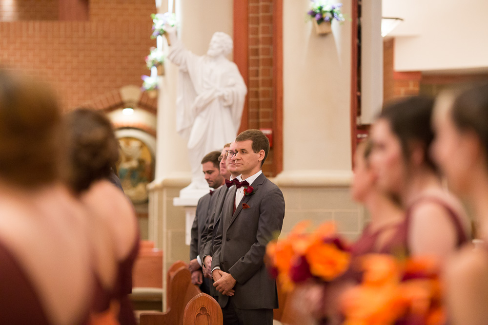 Groomsmen watching the wedding ceremony | Candid wedding photography at Saint Theresa Church in Ashburn