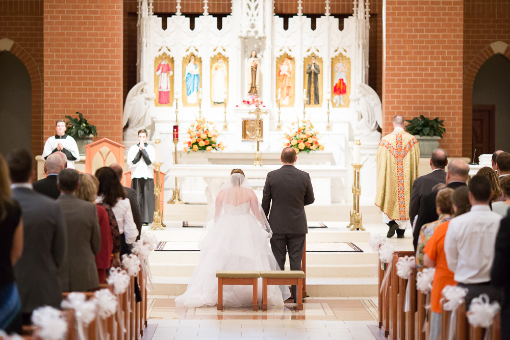 Bride and groom at the altar during their wedding ceremony at St. Theresa Parish in Ashburn | Catholic Wedding Ceremony Locations in Northern Virginia