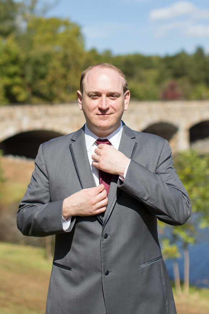 Groom straightening his tie on the wedding day in front of the bridge at the Westin Washington Dulles