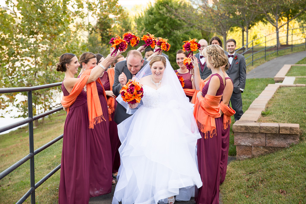 Bride and groom running through the burgundy and orange wedding party