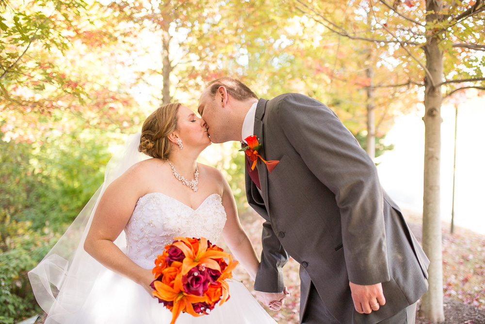 Bride and groom kissing under the fall leaves during their October wedding at the Westin Washington Dulles Hotel