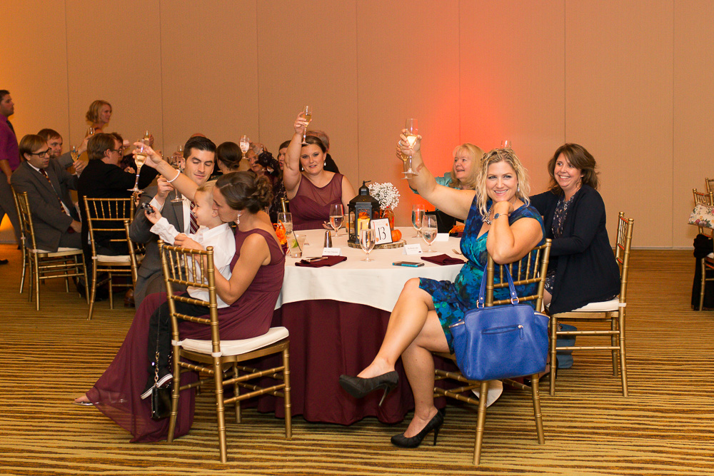 Candid picture of the wedding guests raising their glasses for a toast