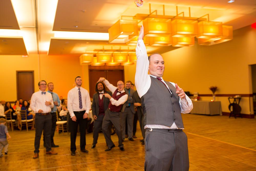 Groom tossing the garter to the single guys on the dance floor
