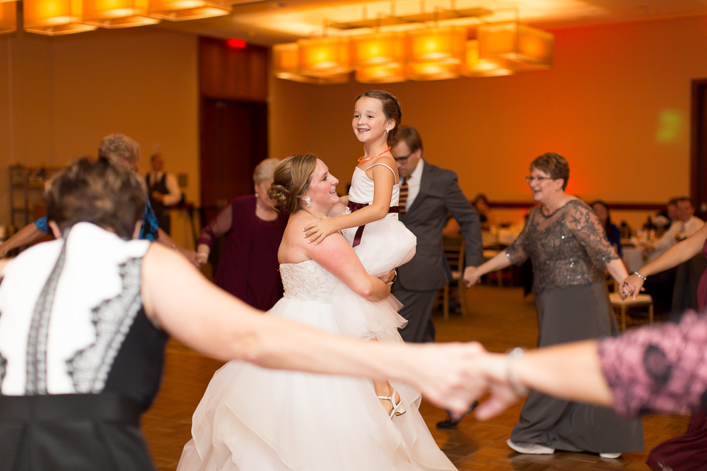 Bride dancing with the flower girl at a Virginia Tech themed wedding | Maroon and orange wedding