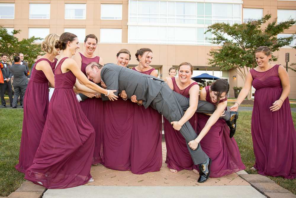 Funny photo of the bridesmaids trying to lift the groom | Burgundy and orange wedding | Northern Virginia Candid Wedding Photographer
