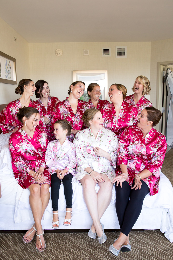 Bride and bridesmaids in matching robes hanging out while getting ready for the wedding day