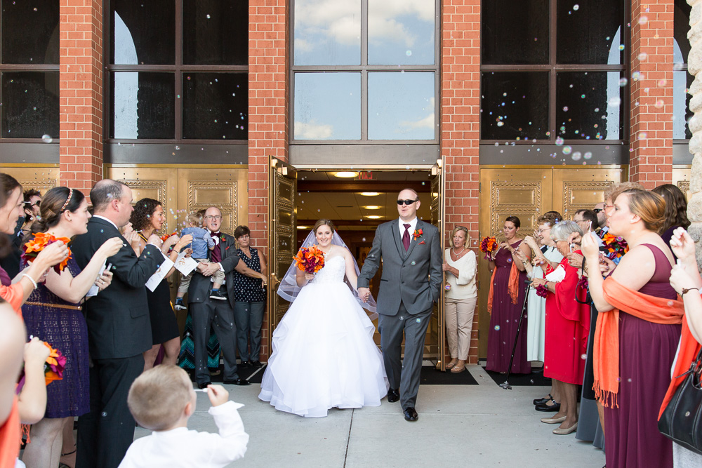 Bride and groom bubble exit from Saint Theresa Catholic Church in Ashburn, Virginia | Ashburn Virginia Wedding Photography