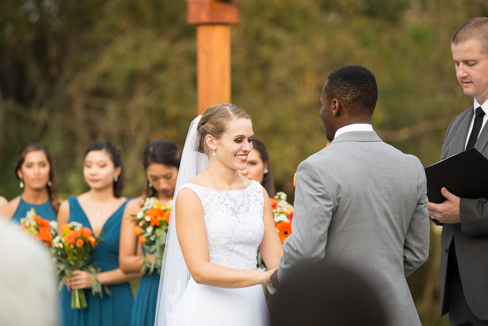 Bride smiling during the outdoor wedding ceremony at Mountain Run Winery | Candid Culpeper Wedding Photographer