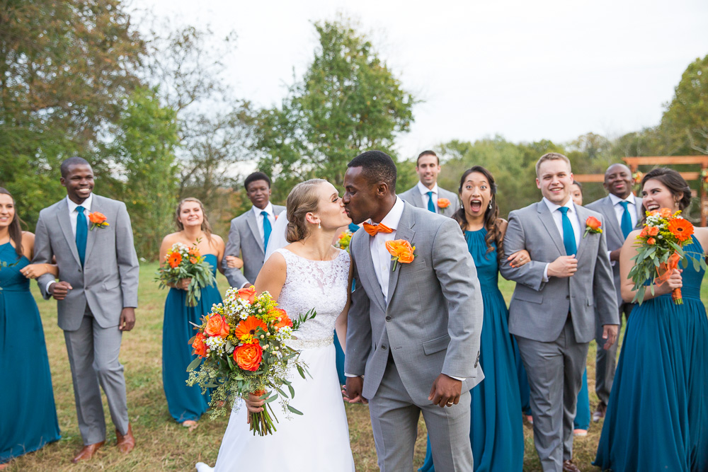 Candid wedding party photo as bride and groom kiss | Culpeper Wedding Photographer