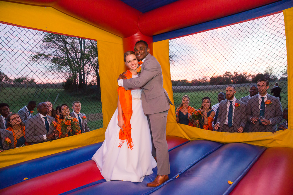 Bride and groom in the moon bounce while bridal party looks on
