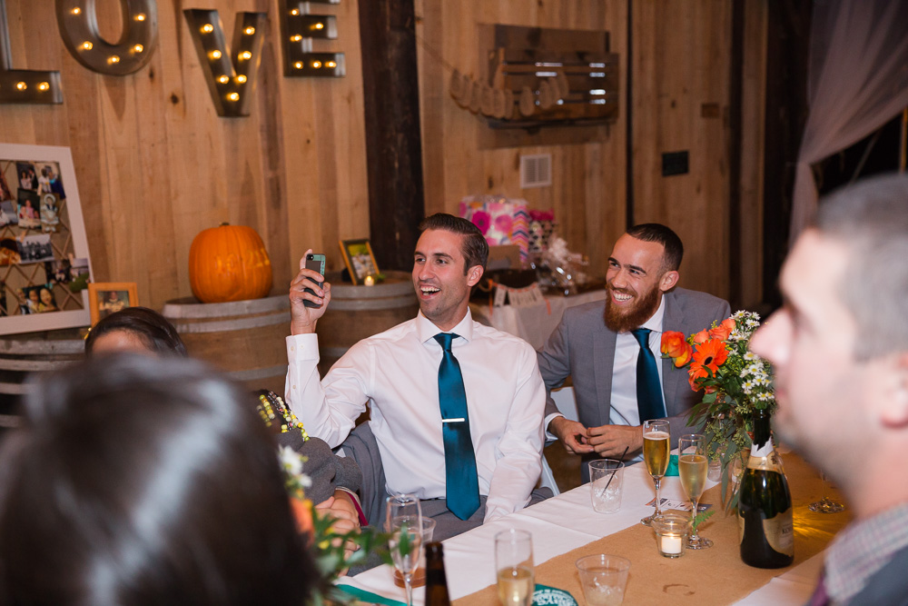 Groomsmen laughing during the best man's toast