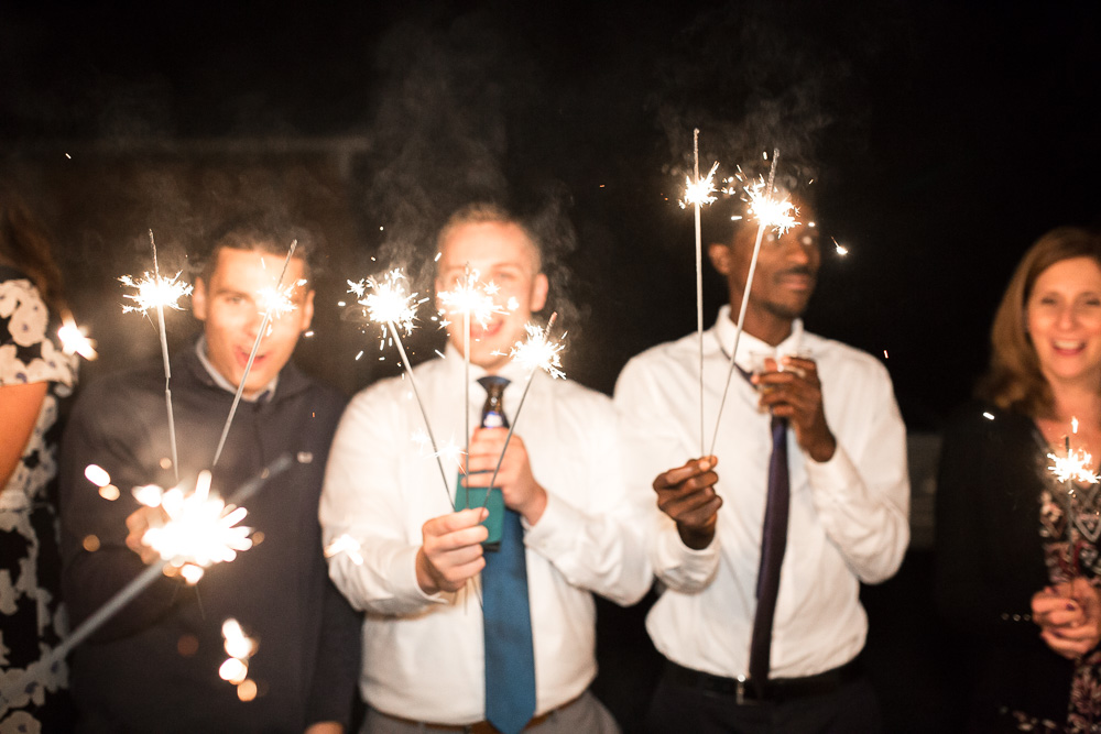 Wedding guests holding sparklers as they wait for bride and groom to exit