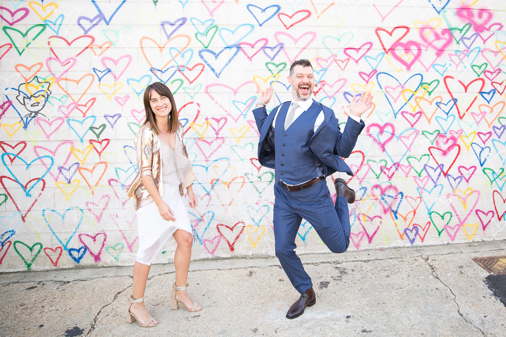 Fun wedding photos at the Union Market heart wall | Candid DC Wedding Photography