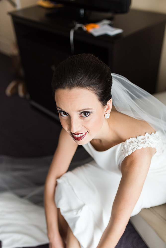 Bride putting on her Badgley Mischka heels at The Strathallan Hotel | Rochester Wedding Photography