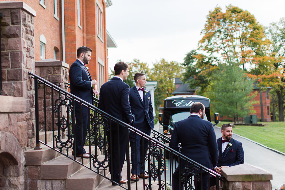 Groom and groomsmen hanging out on the front steps of Chapel Hill | Rochester Wedding Photographer