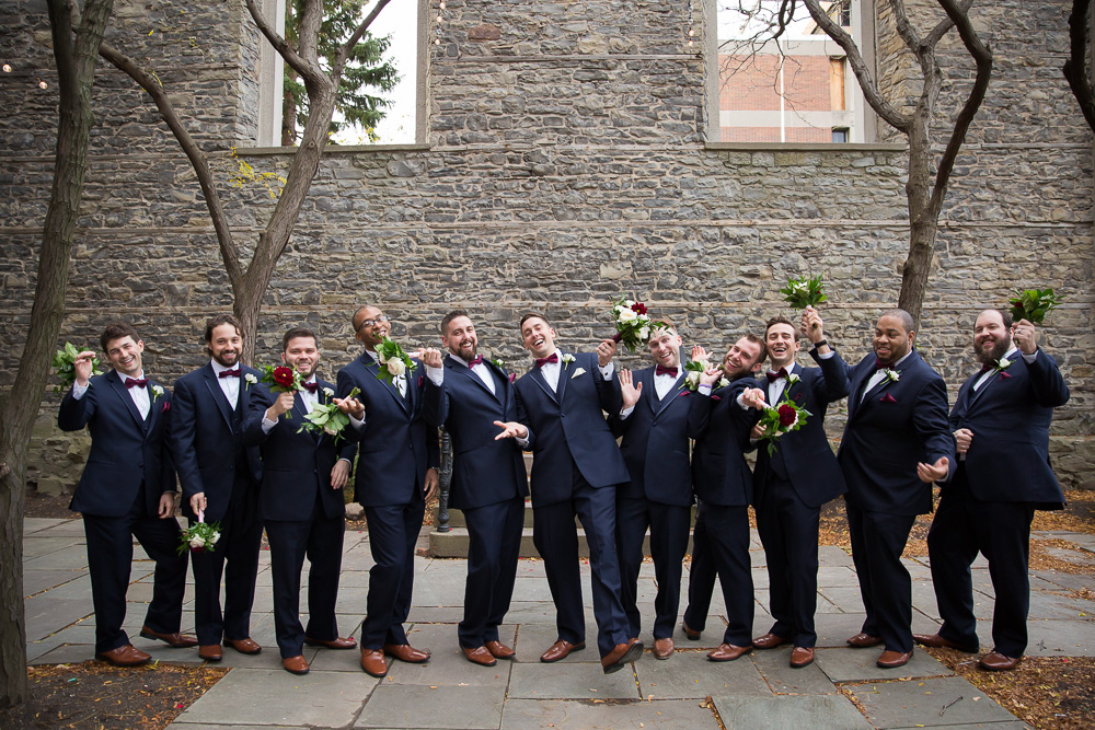 Groom and groomsmen having fun during wedding photos at St. Joseph's Park | Suits from Mens' Wearhouse, Rochester NY