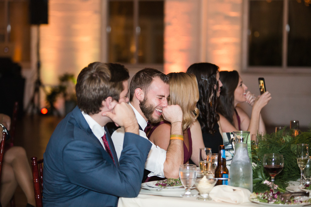 Wedding guests laughing during the toasts | Fun Wedding Photographer in Rochester, New York