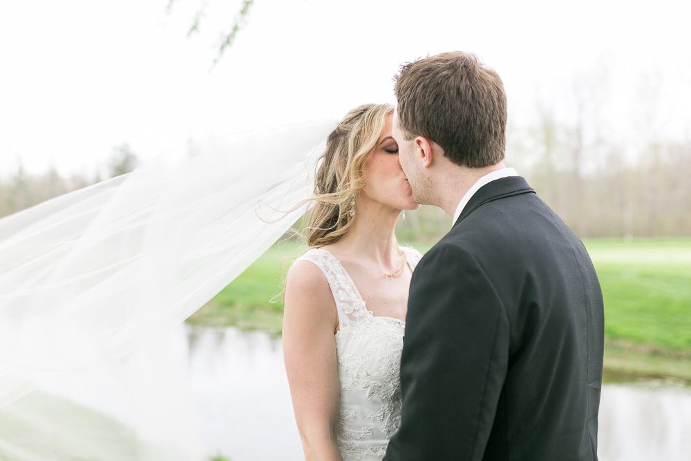 Husband and wife kiss and veil blows in the wind