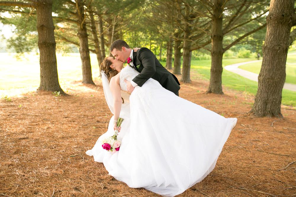 Groom dips the bride during their wedding photos