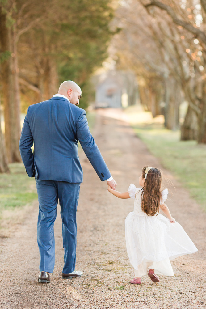 Cute photo of father and daughter holding hands while they walk down the tree-lined path | Candid Northern Virginia Photographer