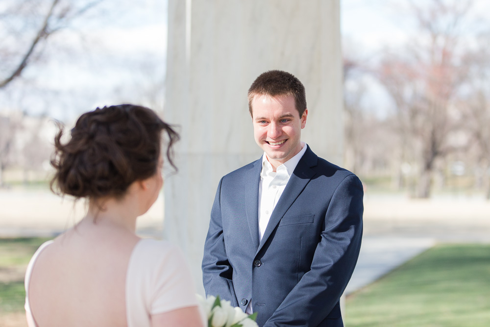 Groom smiling at the bride during their intimate wedding ceremony in Washington, DC | DC War Memorial Wedding