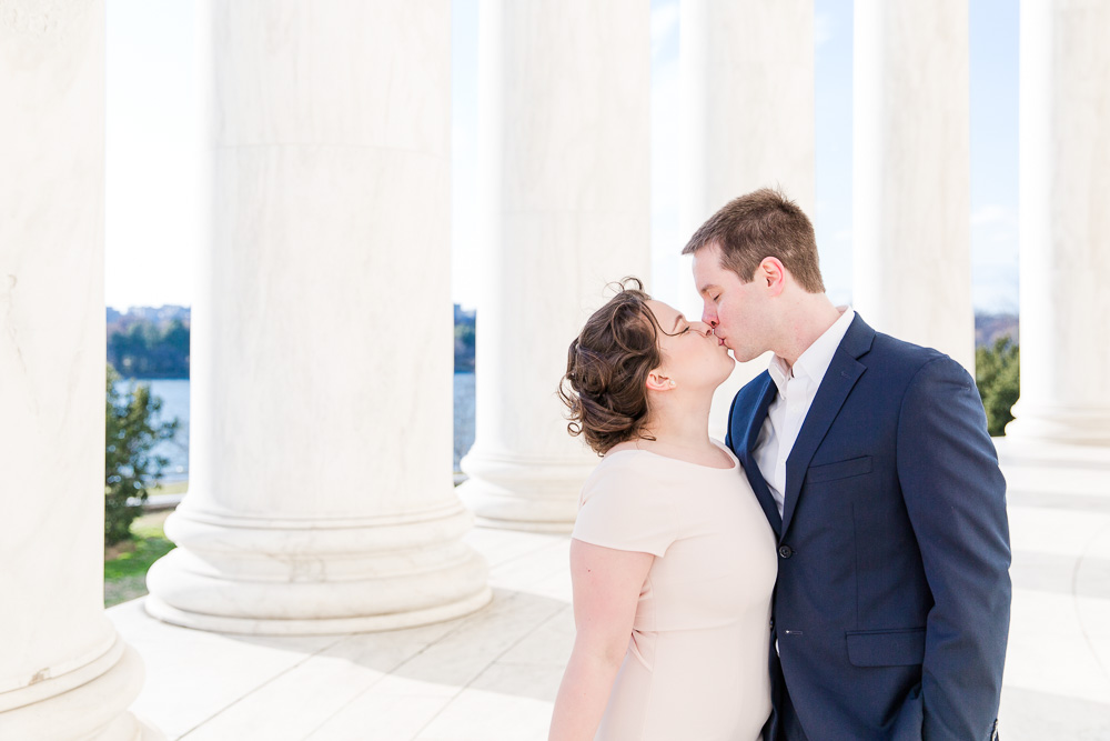 Bride and groom kissing in front of the marble columns at the Thomas Jefferson Memorial in DC