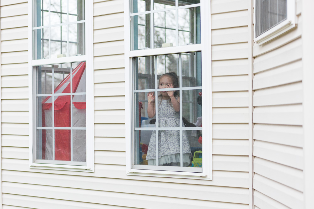 Granddaughter watching the wedding photos through the window | Candid Culpeper Photography