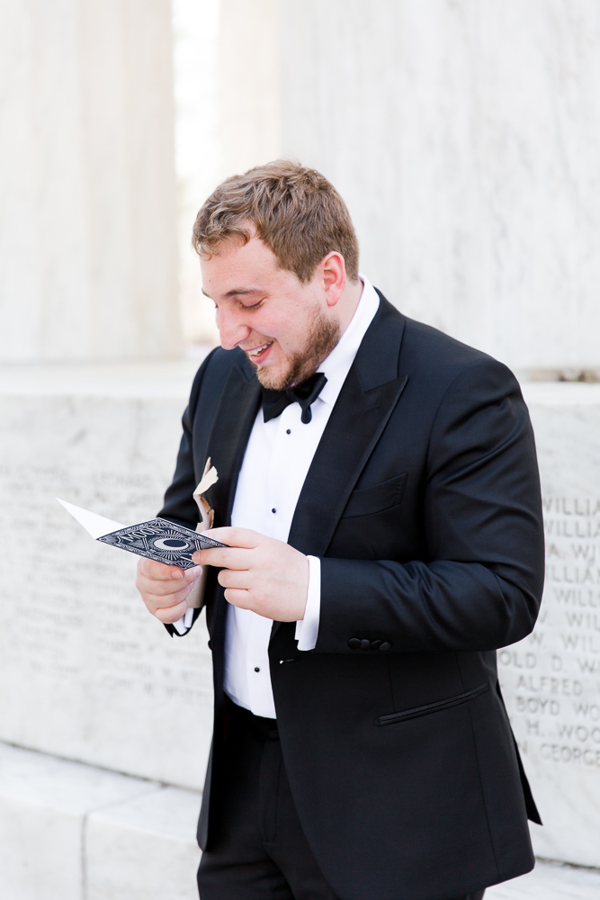 Groom smiling while reading a heartfelt letter from the bride before the wedding ceremony at the DC War Memorial