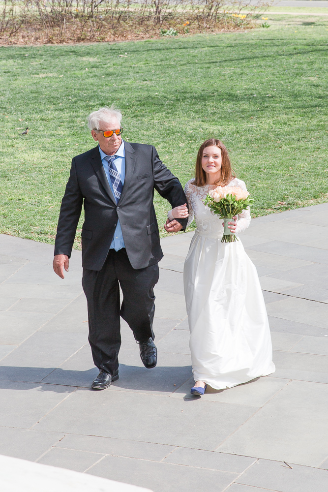 Bride and her father walking down the aisle as they approach the DC War Memorial