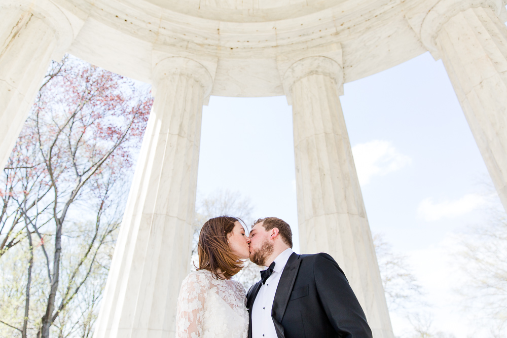 A kiss with the dome of the memorial above the wedding couple