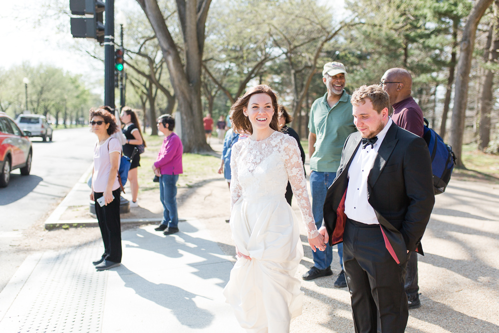 Walking through the crowds of tourists to see the cherry blossoms at the Tidal Basin on their wedding day | Candid Wedding Photographer in Washington, DC